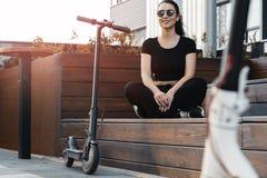 Den unga attraktiva kvinnan som sitter bredvid electrick, sparkar sparkcykeln på modernt parkerar royaltyfri bild
