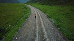 _ den unga attraktiva kvinnliga fotvandraren med ryggsäcken är på en grusväg i bergen Flickahandelsresande Altai Siberia arkivfilmer