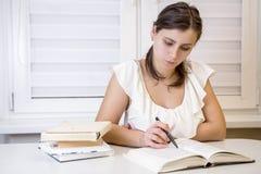 Den unga attraktiva kvinnliga studenten med böcker förbereder sig för examina på universitetet Lär kurser Utbildning hemma Royaltyfria Foton