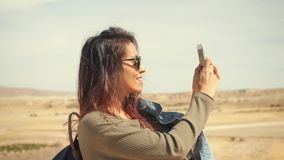 Den unga attraktiva le flickan för det blandade loppet tar det panorama- fotoet av öknen på en mobiltelefon Lycklig turist- kvinn arkivfilmer