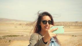 Den unga attraktiva le flickan för det blandade loppet tar det panorama- fotoet av öknen på en mobiltelefon Lycklig turist- kvinn lager videofilmer