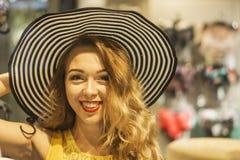 Den unga attraktiva le flickan i gul klänning är den långhåriga sommarhatten för mått i gallerian Arkivfoton