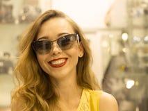 Den unga attraktiva le flickan i gul klänning är måttsolglasögon i gallerian Arkivfoton