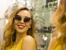 Den unga attraktiva le flickan i gul klänning är måttsolglasögon i gallerian Arkivfoto