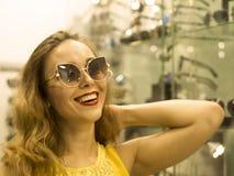 Den unga attraktiva le flickan i gul klänning är måttsolglasögon i gallerian Royaltyfri Foto