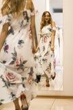 Den unga attraktiva le flickan i gul klänning är den nya klänningen för mått i gallerian Arkivfoton