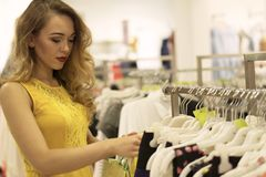 Den unga attraktiva le flickan i gul klänning är väljer modeklänningen i gallerian Arkivfoton