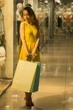 Den unga attraktiva le flickan i gul klänning går i gallerian med shoppingpåsar Arkivfoton