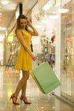 Den unga attraktiva le flickan i gul klänning går i gallerian med shoppingpåsar Royaltyfri Foto