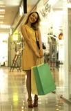 Den unga attraktiva le flickan i gul klänning går i gallerian med shoppingpåsar Royaltyfria Foton