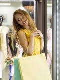 Den unga attraktiva le flickan i gul klänning går i gallerian med shoppingpåsar Royaltyfri Bild
