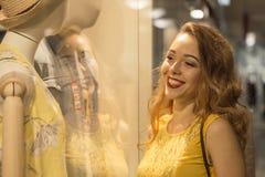 Den unga attraktiva le flickan i gul klänning ser ställa ut i gallerian Royaltyfri Bild
