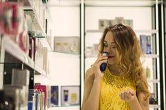 Den unga attraktiva le flickan i gul klänning smakar doft av ny doft i shoppinggallerian Arkivbilder