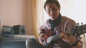 Den unga attraktiva manliga musikern komponerar och antecknar filmmusiken som spelar gitarren genom att använda datoren, fokus på royaltyfria bilder