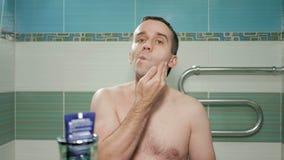 Den unga attraktiva mannen använder en kräm, når han har rakat i badrummet Det är en elektrisk rakning och satte krämen på framsi lager videofilmer