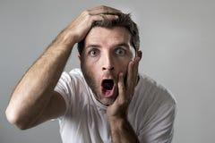 Den unga attraktiva mannen gjorde häpen häpet i uttryck för chocköverraskningframsida och chocksinnesrörelse Arkivfoto