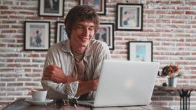 Den unga attraktiva mannen har extra- tid efter arbete, spenderar tid på kafét, blickar directrly in i kamera som sitter på tabel lager videofilmer