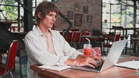 Den unga attraktiva mannen i ljus beklär, använder en bärbar dator, ler och skriver hans tankar till en anteckningsbok, spenderar arkivfilmer