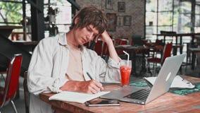Den unga attraktiva mannen i ljuskläder, i ett fundersamt tillstånd, skriver ner hans tankar i en anteckningsbok, spenderar hans  lager videofilmer