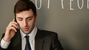 Den unga attraktiva mannen sitter talar på telefonen och drickakaffe i kafé stock video