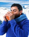 den unga attraktiva mannen som dricker utomhus koppen kaffe i kallt vintersnöberg på jul, semestrar Arkivfoton