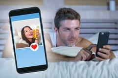 Den unga attraktiva mannen som ligger i säng på linjen som söker för, könsbestämmer eller älskar att finna en härlig flickaprofil Arkivbild