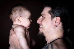 Den unga attraktiva mannen som rymmer ett nyfött, behandla som ett barn studioskottet royaltyfri fotografi