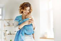 Den unga attraktiva modern ler, och se till och med foto av sonen på att försöka för mobiltelefon överför någon pics till hennes  Arkivbilder