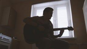 Den unga attraktiva musikern komponerar musik på gitarren och lekar, annat musikinstrument i förgrunden, kontur Royaltyfria Bilder