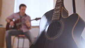 Den unga attraktiva musikern komponerar musik på gitarren och lekar, annat musikinstrument i förgrunden som är suddig Royaltyfri Fotografi