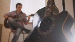 Den unga attraktiva musikern komponerar musik på gitarren och lekar, annat musikinstrument i förgrunden som är suddig arkivfoto