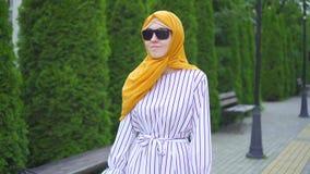 Den unga attraktiva muslim kvinnan som försämras visuellt med en gå rotting i, parkerar upp slut stock video