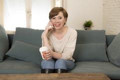 Den unga attraktiva och lyckliga röda hårkvinnan som sitter den hemmastadda soffasoffan som dricker kaffe som talar på mobiltelef Fotografering för Bildbyråer