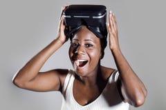 Den unga attraktiva och lyckliga svarta afro amerikanska kvinnan som visar vision för VR 3d, rullar med ögonen, når han har tyckt Arkivfoto