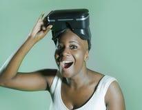 Den unga attraktiva och lyckliga svarta afro amerikanska kvinnan som visar vision för VR 3d, rullar med ögonen, når han har tyckt Fotografering för Bildbyråer