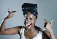 Den unga attraktiva och lyckliga svarta afro amerikanska kvinnan som visar vision för VR 3d, rullar med ögonen, når han har tyckt Royaltyfri Foto