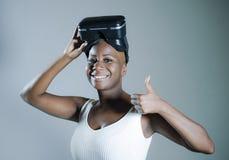Den unga attraktiva och lyckliga svarta afro amerikanska kvinnan som visar vision för VR 3d, rullar med ögonen, når han har tyckt Royaltyfri Fotografi