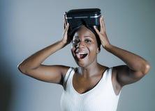 Den unga attraktiva och lyckliga svarta afro amerikanska kvinnan som visar vision för VR 3d, rullar med ögonen, når han har tyckt Royaltyfri Bild
