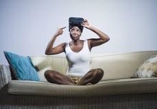 Den unga attraktiva och lyckliga svarta afro amerikanska kvinnan som visar vision för VR 3d, rullar med ögonen, når han har tyckt Arkivfoton