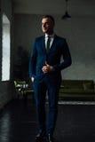 Den unga attraktiva och säkra affärsmannen i blått passar och smokingen Arkivfoton