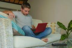 Den unga attraktiva och stiliga lyckliga mannen som sitter den hemmastadda soffasoffan som arbetar med netbook för bärbar datorda royaltyfri fotografi