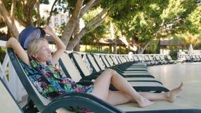Den unga attraktiva sexiga kvinnan i sommarhatt vilar vid pölen stock video