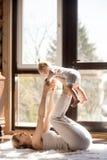 Den unga attraktiva sportiga modern och behandla som ett barn dottern som övar på H Arkivbilder