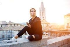 Den unga attraktiva studenten använder celltelefonen under vilar mellan föreläsningar i universitet Royaltyfria Foton