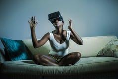 Den unga attraktiva svarta afro amerikanska kvinnan som spelar den förbluffade och förvånade virtuell verklighetvideospelet som b royaltyfri bild