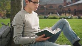 Den unga avkopplade grabben läser modern fiktion som sitter på den bara högskolan för plädet lager videofilmer
