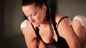 Den unga böjliga kvinnlign som gör yoga, poserar stock video