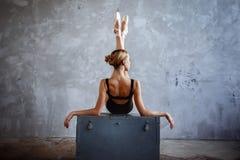 Den unga ballerina i en svart dansdräkt poserar i en vindstudio Arkivbilder