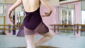 Den unga ballerina i purpurfärgad body utför elegantly bestämda balettövningar, piruetterar vid femte positioner, i balett arkivfilmer