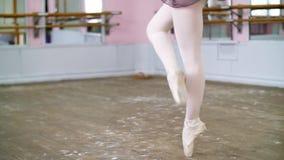 Den unga ballerina i purpurfärgad body utför elegantly bestämda balettövningar, piruetterar vid femte positioner, i balett lager videofilmer